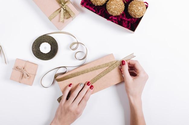 Weibliche hände mit roter maniküre packen die geschenke in kartons und binden sie mit bändern