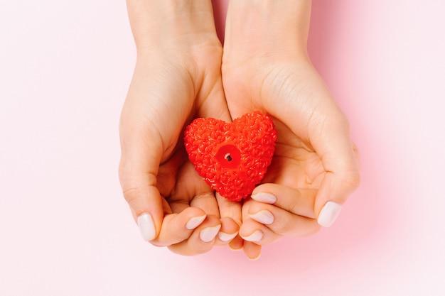 Weibliche hände mit sanfter maniküre halten eine herzförmige kerze. rosa hintergrund und st.valentine tageskonzept.