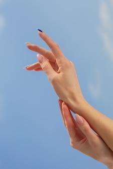 Weibliche hände mit schöner maniküre auf blauem himmelshintergrund