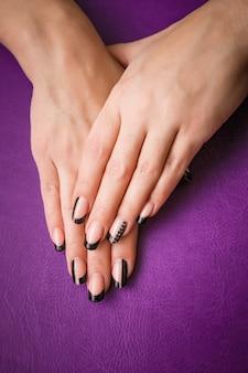 Weibliche hände mit schwarzer maniküre auf veilchen