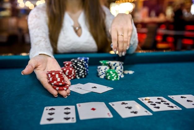 Weibliche hände mit spielkarten und pokerchips