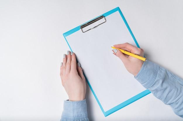 Weibliche hände mit stift auf dokument. frau unterschreibt auf papier. draufsicht