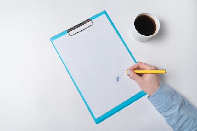 Weibliche hände mit stift auf dokument und tasse kaffee. frau unterschreibt auf papier