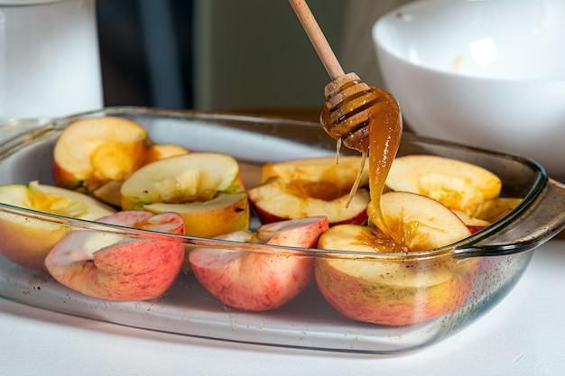 Weibliche hände mit stock, der äpfel mit honig in einem glasbehälter gießt und sie für das kochen, hausgemachtes wüstenkonzept vorbereitet