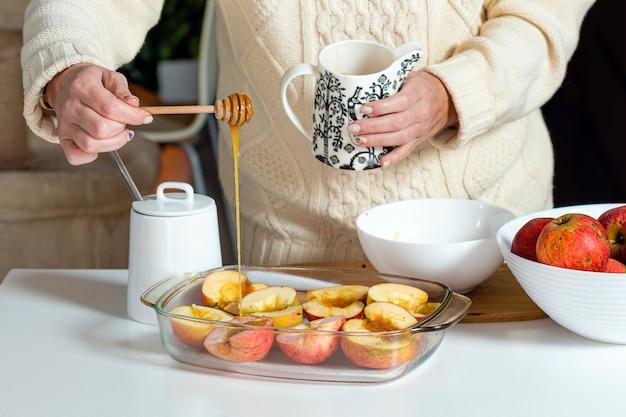 Weibliche hände mit stock gießen äpfel mit honig in einem glasbehälter und bereiten sie für das kochen vor, hausgemachtes wüstenbackkonzept