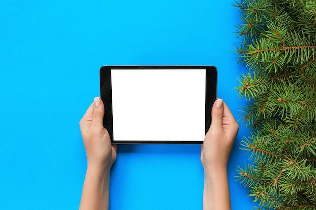 Weibliche hände mit tablet-computer auf rosa weihnachtsoberfläche.