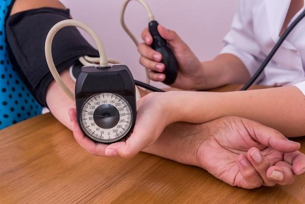 Weibliche hände mit tonometer, der den blutdruck misst