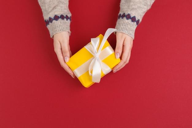 Weibliche hände mit weihnachtsgeschenk auf rot