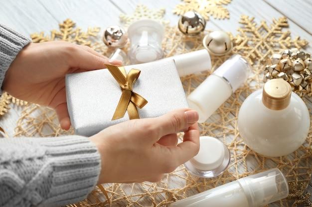 Weibliche hände mit weihnachtsgeschenk- und schönheitskosmetikprodukten auf dem tisch