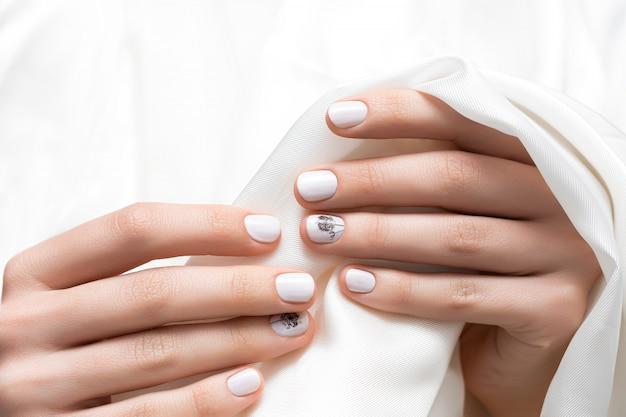 Weibliche hände mit weißem nageldesign, nahaufnahme.