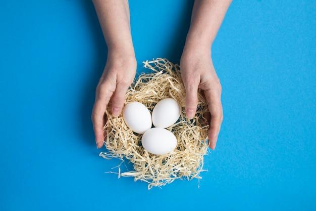 Weibliche hände mit weißen hühnereiern in einem strohnest auf der blauen oberfläche