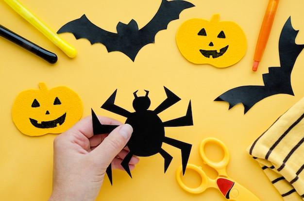 Weibliche hände nähen, halloween-dekorationen malen. handgemachter kürbis, schwarze fledermaus, spinne auf orange oberfläche.