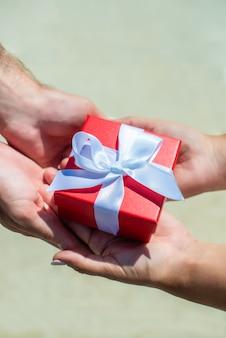 Weibliche hände nehmen ein geschenk von männlichen händen an. auf der straße geben sie eine rote kiste mit einer weißen schleife.