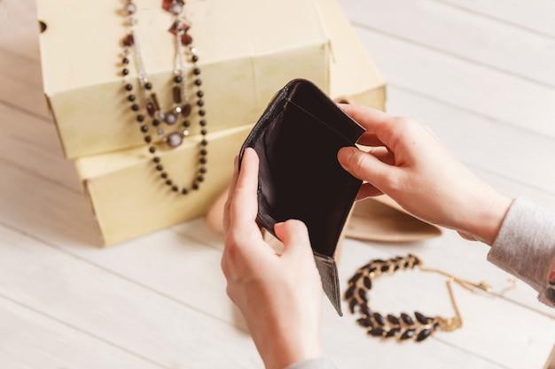 Weibliche hände öffnen den leeren geldbeutel gegen frauenkleidung und -zubehör nach dem einkauf.