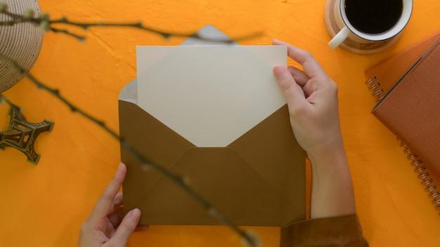 Weibliche hände öffnen einladungskarte auf kreativem schreibtisch