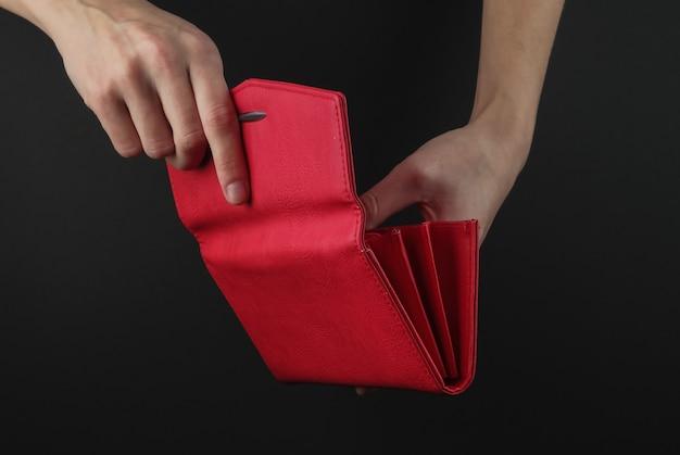 Weibliche hände öffnen rote lederhandtasche auf einem schwarzen hintergrund