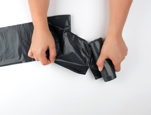Weibliche hände reißen eine schwarze tasche für einen behälter von einer rolle ab