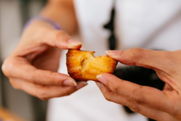 Weibliche hände reißen frisch gebackene canelés.