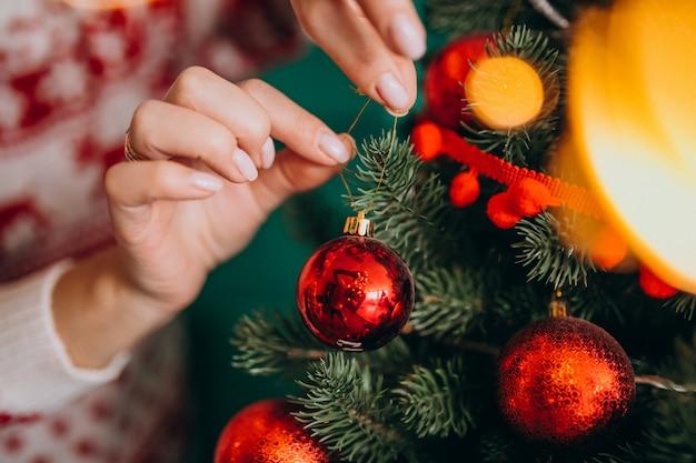 Weibliche hände schließen oben und verzieren weihnachtsbaum mit roten bällen