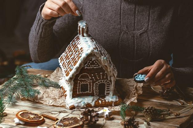 Weibliche hände schmücken das weihnachts-lebkuchenhaus