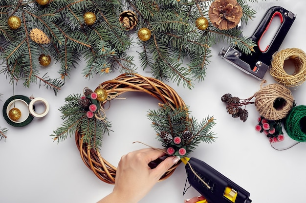 Weibliche hände schmücken den weihnachtskranz mit fichtenzweigen mit einer roten beere und waldkegeln...