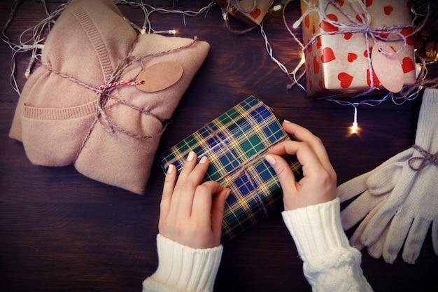Weibliche hände schmücken weihnachtsgeschenkbox