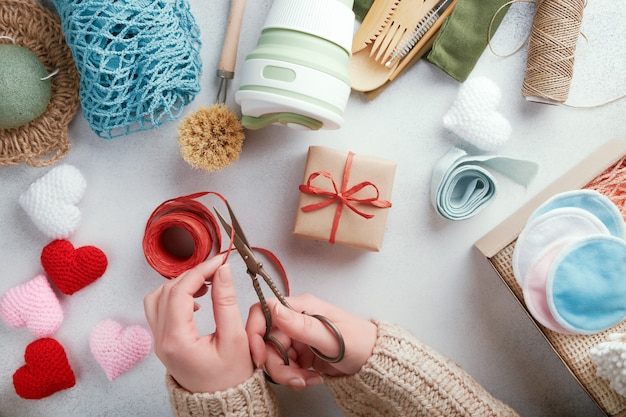 Weibliche hände schneiden bastschnur. set öko-geschenke auf dem tisch.