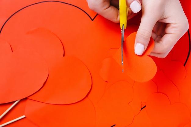 Weibliche hände schneiden ein rotes herz mit einer schere auf einem roten papierhintergrund. vorbereitung auf den urlaub.