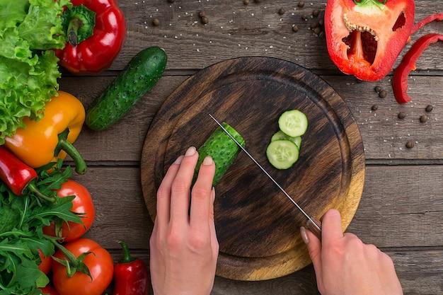 Weibliche hände schneiden gurke am tisch, ansicht von oben. auf dem tisch gemüse und ein holzbrett