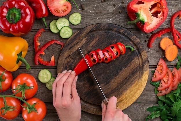 Weibliche hände schneiden peperoni am tisch, ansicht von oben. auf dem tisch gemüse und ein holzbrett