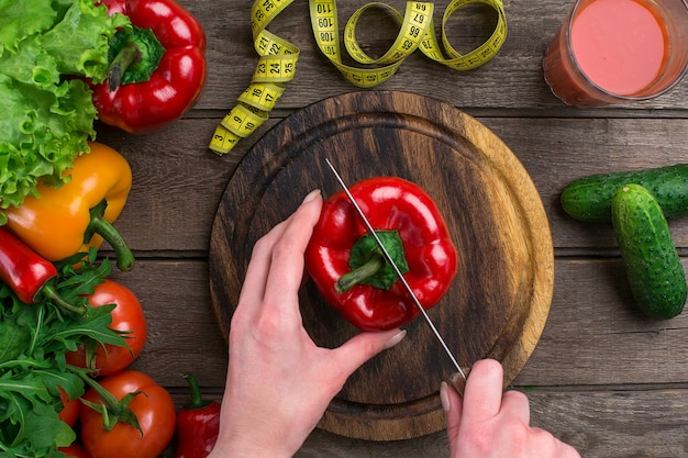 Weibliche hände schneiden pfeffer am tisch, ansicht von oben. auf dem tisch salatblätter, paprika, ein glas tomatensaft, ein holzbrett und ein messer