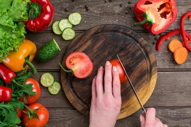 Weibliche hände schneiden tomaten am tisch, ansicht von oben. auf dem tisch gemüse und ein holzbrett