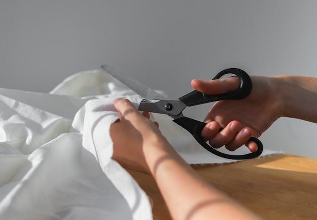 Weibliche hände schneiden weißes baumwolltuch mit nähschere nahaufnahme