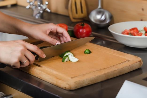 Weibliche hände schnitten eine gurke auf dem brett