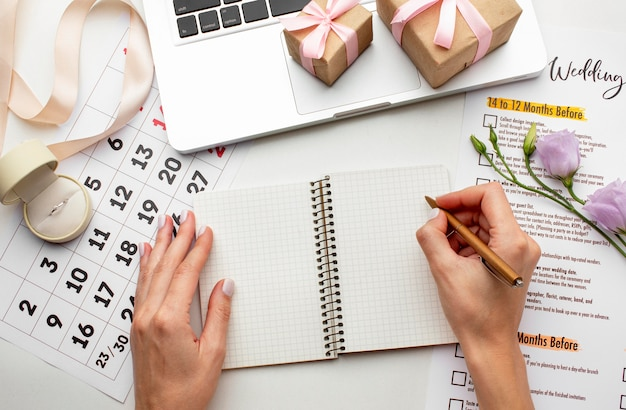 Weibliche hände schreiben auf eine notizbuch-draufsicht