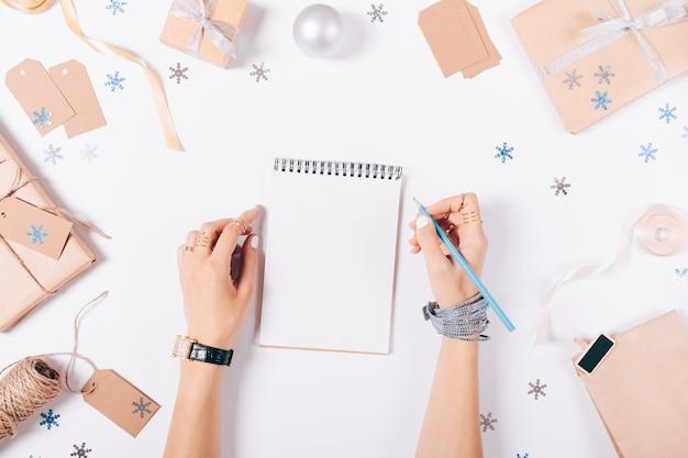 Weibliche hände schreiben eine einkaufsliste in ein notizbuch