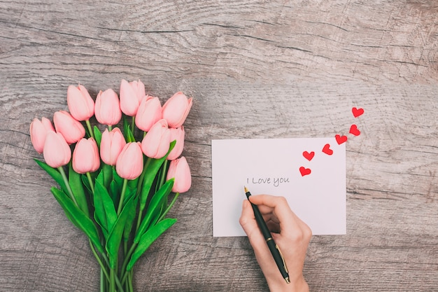 Weibliche hände schreiben eine liebesbotschaft auf einen weißen umschlag auf einem hölzernen hintergrund. valentinstag