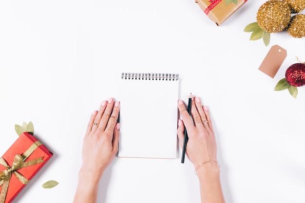 Weibliche hände schreiben in ein notizbuch