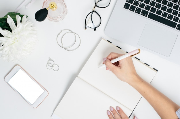 Weibliche hände schreiben in notizbuch auf eine weiße tabelle mit einem telefon der tastatur und des leeren bildschirms