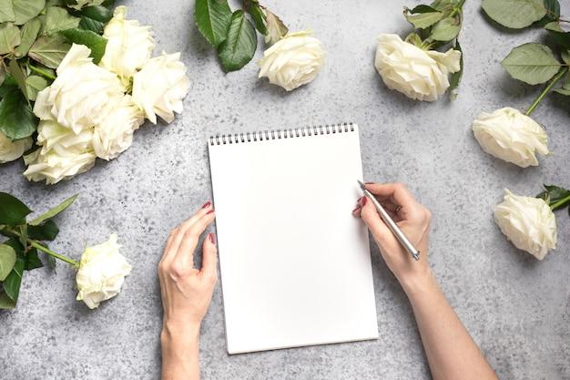 Weibliche hände schreiben in notizbuch und strauß weiße rosen auf grau. draufsicht mit kopierraum.