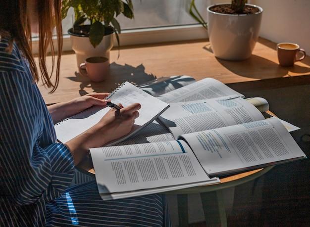 Weibliche hände schreiben mit stift im notizbuch notizen zum studium mit akademischem lehrbuch hautnah
