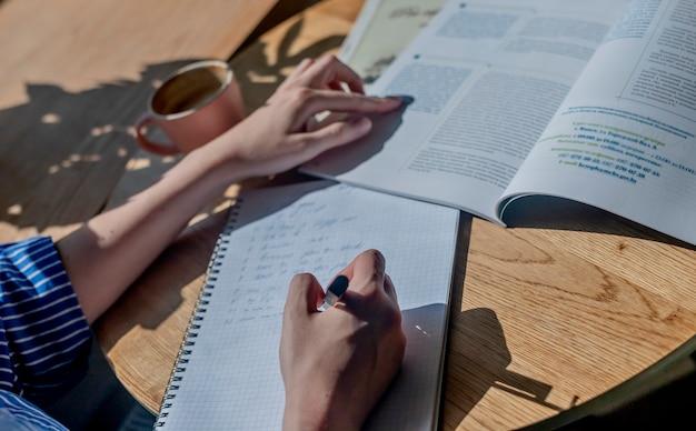Weibliche hände schreiben mit stift in notizbuch notizen lernen mit lehrbuch hautnah