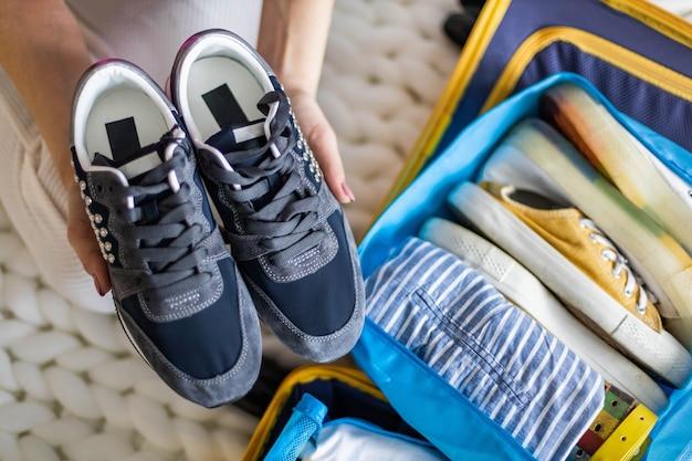 Weibliche hände sportturnschuhe, die in den aufbewahrungsbehälter packen und in den koffer für den reiseurlaub legen