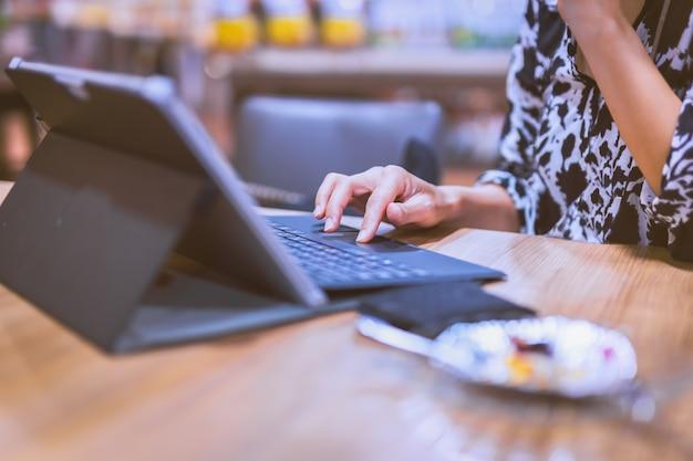 Weibliche hände tippen auf tastaturmaus des laptops im café
