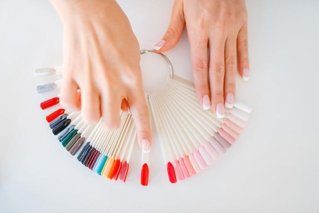 Weibliche hände und bunte nagellackpalette
