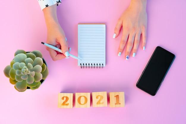 Weibliche hände und offener notizblock auf rosa hintergrund
