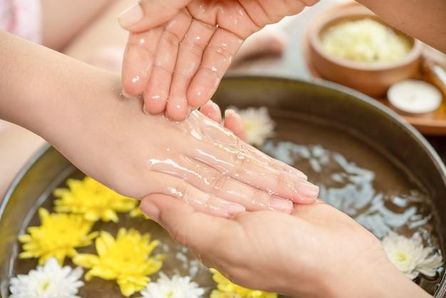 Weibliche hände und schüssel des spa-wassers mit blumen, nahaufnahme. hände spa.