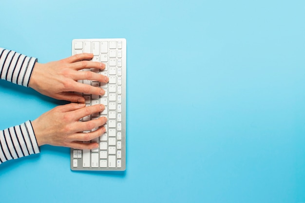 Weibliche hände und tastatur auf einem blauen hintergrund. konzeptarbeitsbereich, arbeit am computer, freiberuflich tätig, design.