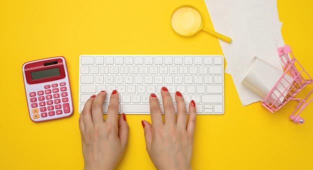 Weibliche hände und weiße drahtlose tastatur, stapel papierquittungen und lupe auf gelbem hintergrund, budgetanalysekonzept, einsparungen