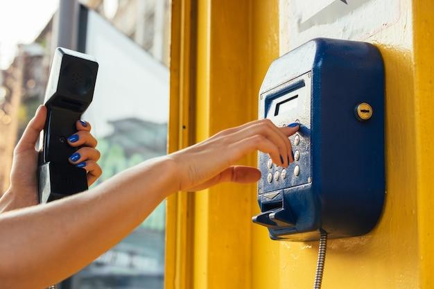 Weibliche hände unter verwendung des münztelefons in der stadt